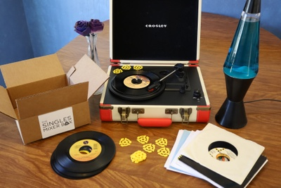A portable record playing and lots of records from a The Singles Mixer subscription box.
