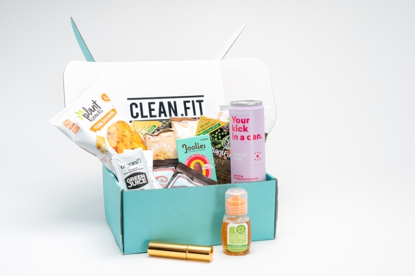An open CLEAN.FIT subscription box filled with healthy snack and drinks.