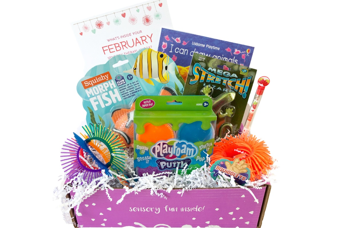 An open Sensory TheraPLAY subscription box filled with play foam putty, a squishy morph fish, a drawing guide book and more.
