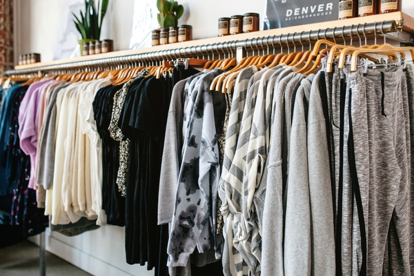 A rack of women's clothing with a shelf above it with jars on it. This where the Judith and Joe subscription box comes from.