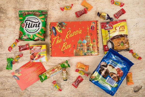 A food subscription box labeled The Russian Box is surrounded by Russian candies, snacks and treats in colorful packaging.