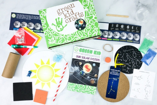 A Green Kid Crafts subscription box surrounded by astronomy cards, a crayon, colored paper and other craft items.