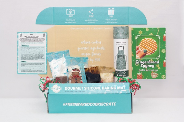 An open Fresh Baked Cookie Crate subscription box with a silicone baking mat, recipe cards, and baking supplies.