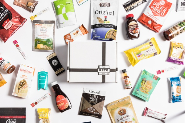 A subscription box labeled The Keto Box near keto-friendly snacks including chocolate syrup, pork panko, and flax crackers.