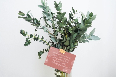 Eucalyptus branches in a vase with a card on the front with encouraging words for mothers.