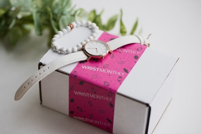 A small, white box with a pink wrapper labeled Wrist Monthly. There is a white and gold watch and a white bracelet on it.