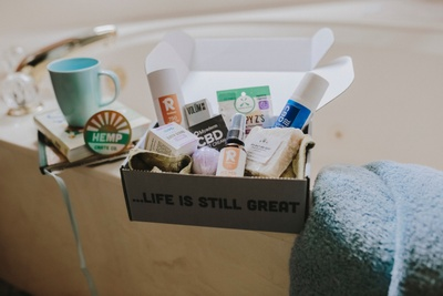On a bathtub sits an open subscription box labeled Life is Still Great, featuring premium CBD products like gummies.
