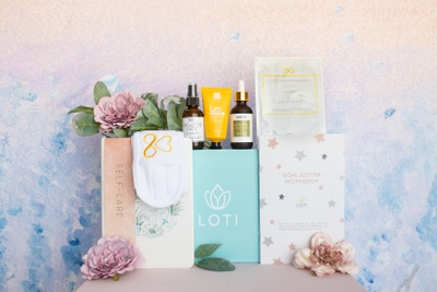 A Loti Wellness Self-Care subscription box surrounded by a Goal Getter workbook, a fragrance spray and lotion.