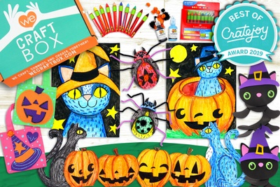 A We Craft Box surrounded by Halloween crafts and drawing including jack-o-lanterns and black cats.