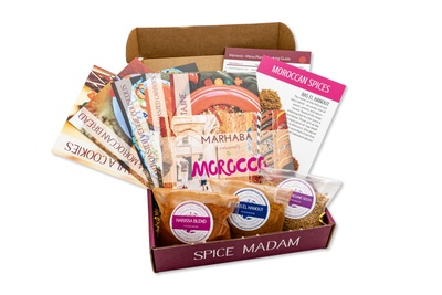 An open food subscription box labeled Spice Madam that is filled with 3 bags of spices and lots of recipe cards.