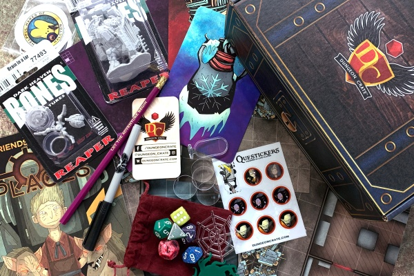A Dungeon Crate subscription box  with dice, cards, a figurine, books a pencil and a marker.