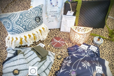Items from The Appalachian Artisan subscription box including a decorative pillow, necklaces, women's clothing and more.