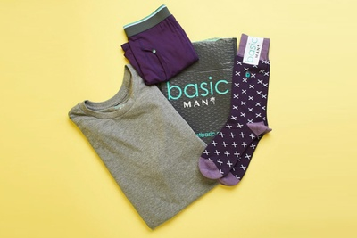 A package that says Basic Man, a gray T-shirt, purple and gray boxer briefs and purple socks on a yellow background.
