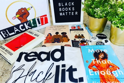 Books, a tote bag, a box with the black power fist holding a pencil and the word BlackLit, a felt board, and stickers.
