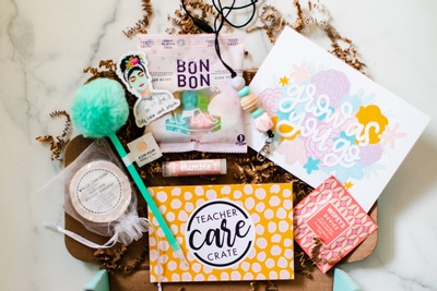 An open Teacher Care Crate subscription box filled with bon bons, an encouraging card, lip balm and a pom pom pen.