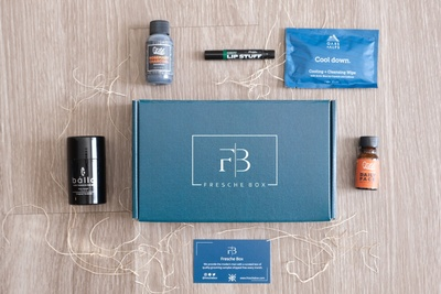 A closed, blue Freshe subscription box surrounded by quality grooming samples for men.