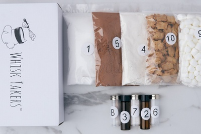 A white subscription box called Whisk Takers with clear bags full of baking mixes and ingredient vials.