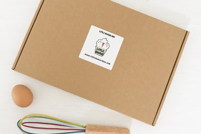 A baking subscription box labeled Little Bakers with a brown egg and a colorful whisk.