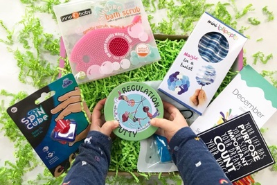 A young child's hands hold a round tin that says Regulation Putty over a subscription box with a spin cube and bath scrub.