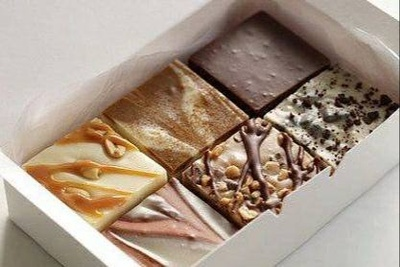A small, white box filled with 6 pieces of different types of fudge from Nellie's Sweet Shoppe.
