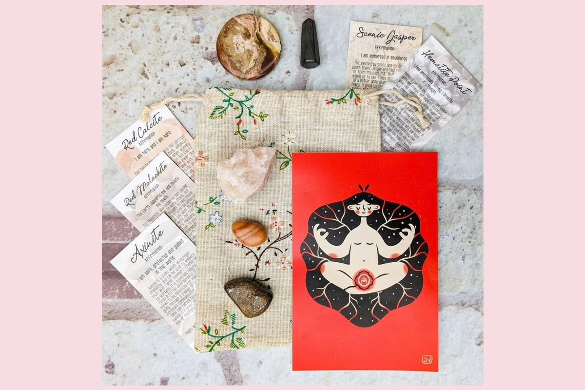 Items from an Awakening in a Box subscription box, including healing crystals and informational cards about the crystals.