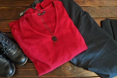 The contents of a Reborn: An Upscale Consignment Experience subscription box which are a red sweater, black pants and boots.