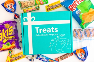 A Treats subscription box surrounded by Ruffles potato chips, Takis, gum, candy, lollipops and other treats.