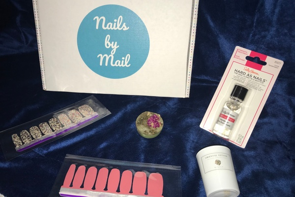 A Nail Obsession subscription box that says nails by mail and various nail stickers and top coat for nails.