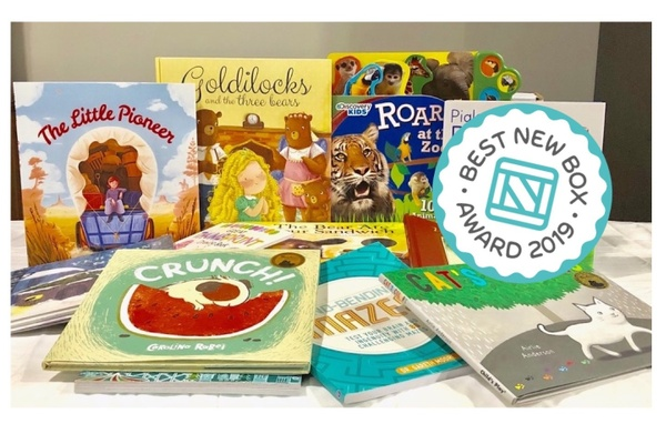 Several children's books on a table, some stacks, some standing up. With a best new box award.