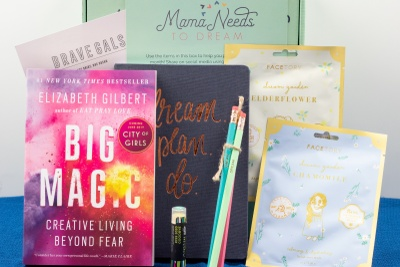A Mama Needs subscription box sitting behind a self-help book, a dream journal, pencils, lip balm and beauty products.