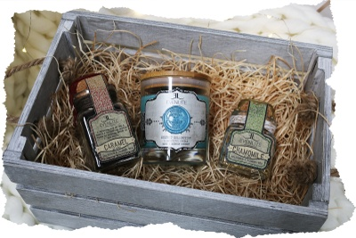 A small, gray crate containing a jar of caramel, a jar of chamomile, and a jar candle.