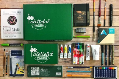 A green Paletteful Pack subscription box surrounded by art supplies including paint, brushes, markers and paper.