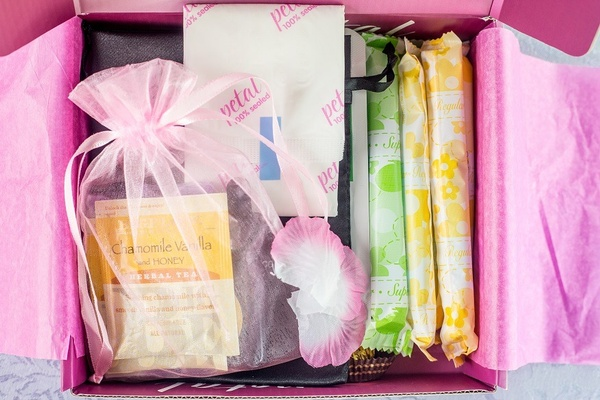 A pink subscription box opened to show tampons, pads, flower petals and a small bag with different types of tea.