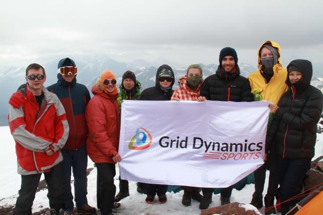 Grid Dynamics team on Elbrus with a brand flag
