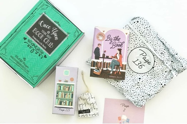 A green Once Upon a Book Club subscription box lies next to a novel along with 4 wrapped gifts with page numbers.