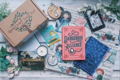 A SpearCraft Book subscription box with books, a necklace, a candle and other decorations.