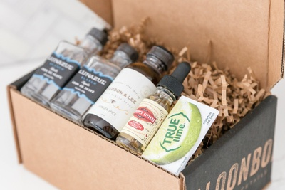 A SaloonBox DIY Cocktail Kit subscription box open and filled with bottle of alcohol.