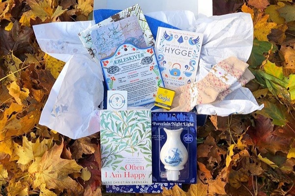 A Bibliophilic Excursions subscription box filled with books, a pair of socks and other items for a literary journey.