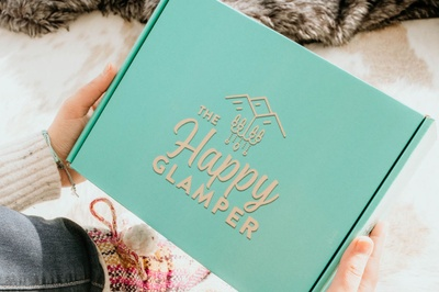 A woman holding a mint green subscription box labeled The Happy Glamper.