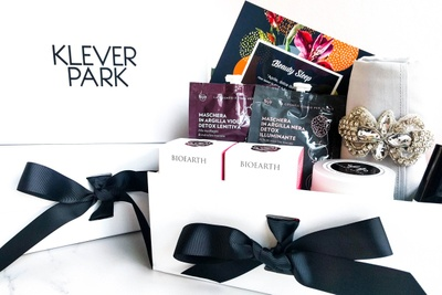 A Kleverpark subscription box with skincare items from BioEarth and a silver facial towel held by a sparkly diamond brooch.