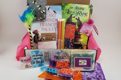 An open beTWEEN the Bookends subscription box filled with kids books, fun pencils, bookmarks, stamps and more.