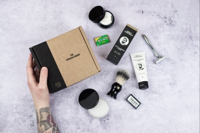 A hand hold a closed Shaving Club subscription box with a razor and other shaving products around it.
