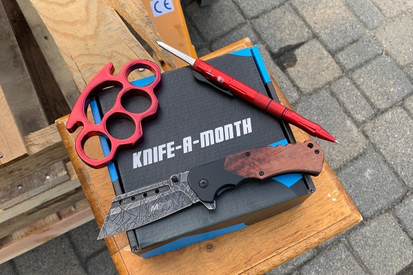A black Knife a Month subscription box sits on a wooden pedestal with a pen knife, a hunting knife and brass knuckles on it.