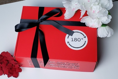 A 180 degree subscription box that is red and has a black ribbon around it with white and red flowers on it.