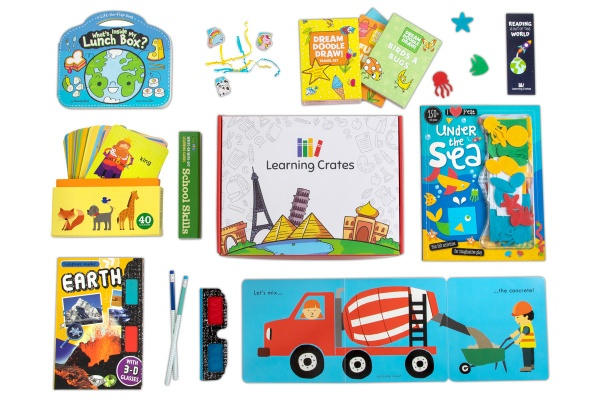A Learning Crates subscription box surrounded by children's books, 3D glasses, and 2 pencils.