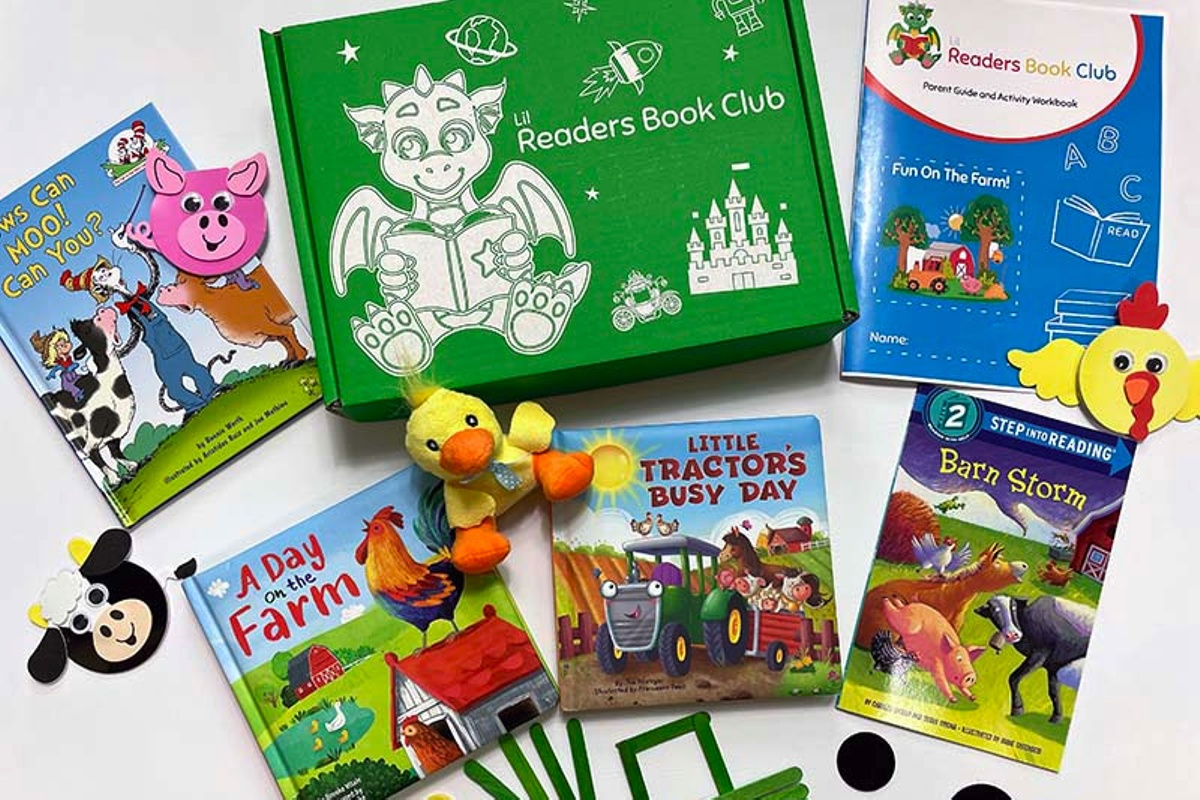 A green, Lil Readers Book Club subscription box with several kids books, a duck toy and chicken, pig and cow cutouts.