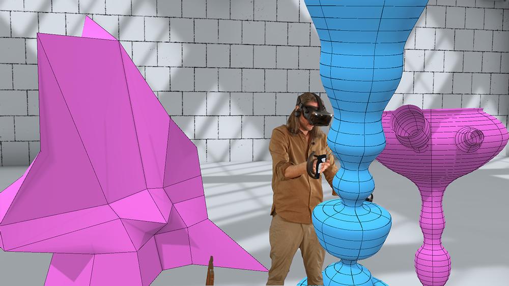 En person med VR-headset och kontroller står och skulpterar färgglada former i ett stort virtuellt rum.