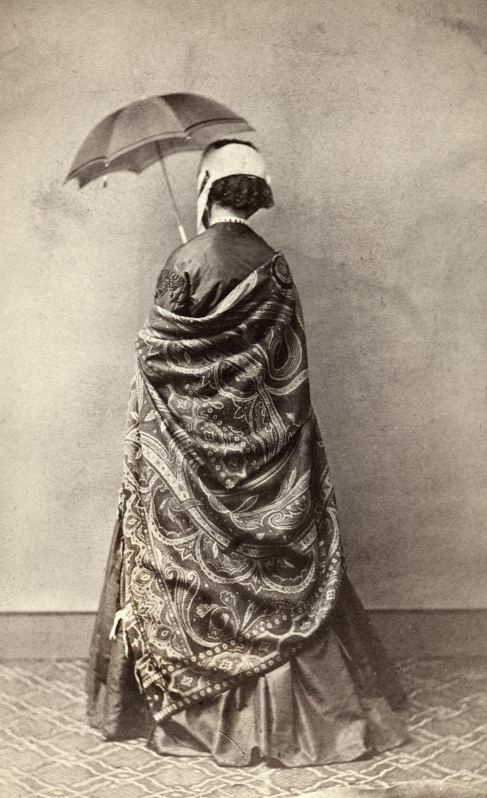 """Fotografi från 1860-talet med en kvinna i stor, mönstrad schal, mörk sidenklänning, ljus hätta med svart spets och parasoll. Enligt texten på baksidan vägrade hon att visa sitt ansikte: """"alla böner och öfvertalningsförsök otillräckliga"""".                                                                                                                 Fotograf Hilda Thysenius, Ronneby, 1860-talet. Gåva av Annie Olins sterbhus 1961.  Albuminsilverfotografi monterat på kartong. Visitkort."""