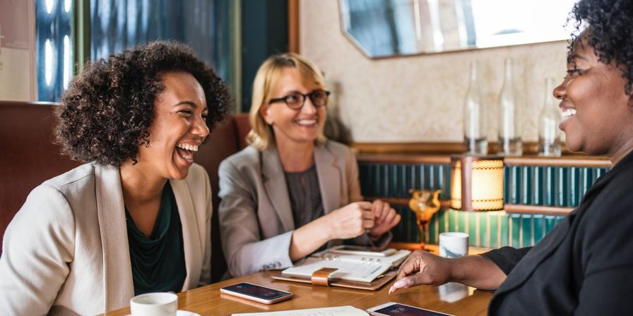A group of women laughing around a table