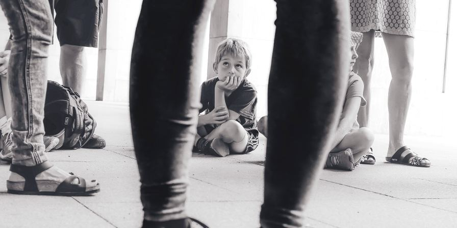 A child sitting on the floor looking up at adults